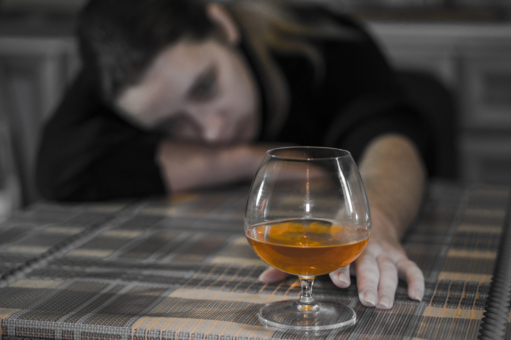 Female alcoholism. Young woman relaxes at home with a glass of drink. The hand reaches for a glass of cognac.